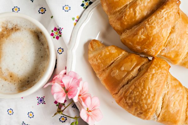 croissants, coffee cup, flower in romantic style